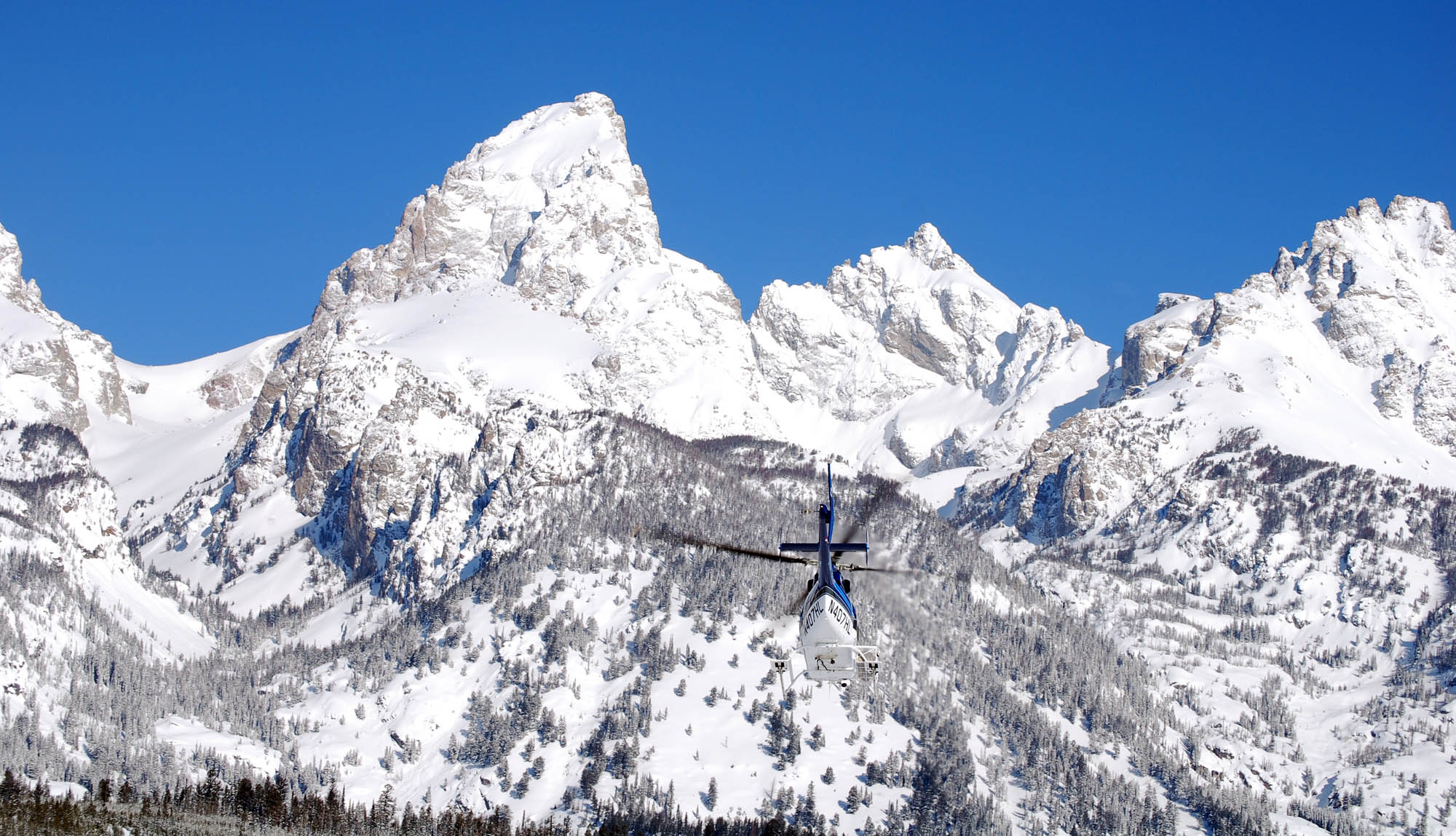 A helicopter heads toward Garnet Canyon in this file photo from April 2011 taken during a search for two lost skiers in Grand Teton National Park. Two snowboarders were rescued Feb. 13 after mistakenly riding into Granite Canyon. (National Park Service photo by Jackie Skaggs — click to enlarge)
