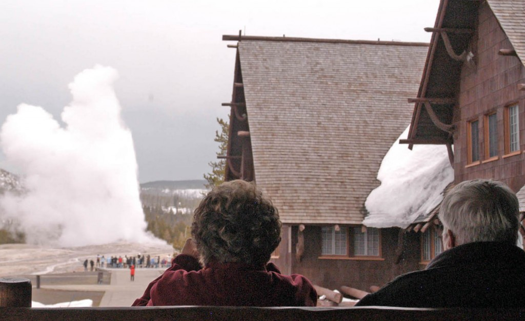 Visitors watch Old Faithful geyser erupt from a second-floor observation deck at the Old Faithful Inn. (Ruffin Prevost/Yellowstone Gate - click to enlarge)