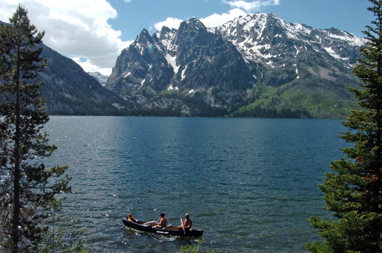 A group paddles a canoe on Jenny Lake in Grand Teton National Park.