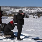 Photographers in Yellowstone National Park snap pictures in January during an eruption of Old Faithful geyser. (Ruffin Prevost/Yellowstone Gate - click to enlarge)