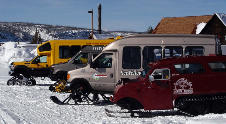 Snow coaches are parked near the Old Faithful Visitor Center in Yellowstone National Park.