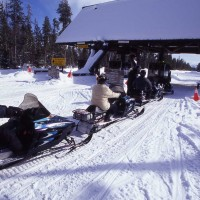 Snowmobile riders in 1998 line up at the West Gate as they wait to enter Yellowstone National Park. (Jim Peaco photo - click to enlarge)