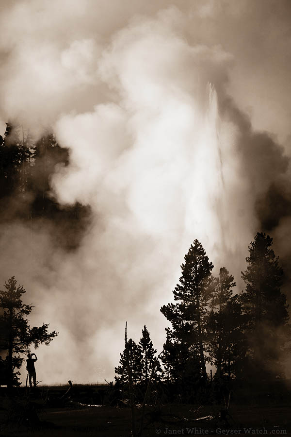 A Yellowstone Park visitor enjoys a second burst from Grand Geyser. (©Janet White - click to enlarge)