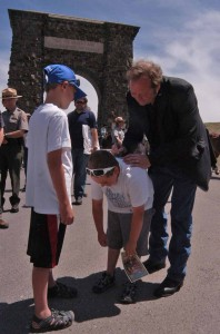 Montana Gov. Brian Schweitzer signs autographs for Landon Guengerich, 7, and Evan Guengerich, 9, left, in front of the Roosevelt Arch in Yellowstone National Park. (Ruffin Prevost/Yellowstone Gate - click to enlarge)