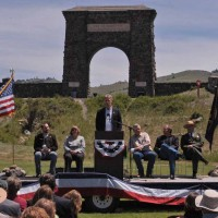 Bill Berg, president of the Greater Gardiner Community Council, speaks in front of the Roosevelt Arch during the Gardiner Gateway Project kickoff event Thursday. Joining him on stage were, from left, Daniel Bierschwale, President, Gardiner Chamber of Commerce; Clara Conner, Division Engineer, Western Federal Lands Highway Division; Marty Malone, Commissioner, Park County, Mont.; Brian Schweitzer, Governor of Montana; and Dan Wenk, Superintenden of Yellowstone National Park. (Ruffin Prevost/Yellowstone Gate - click to enlarge)