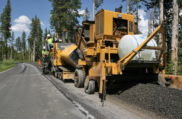 Contractors in 2009 resurface part of an 11-mile stretch of road in Yellowstone National Park between the Lewis River Bridge and the park's South Entrance. Yellowstone road closures are planned as part of summer 2012 construction projects around the Tower and Canyon areas. (NPS photo by Jim Peaco)