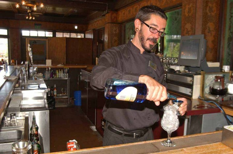 Topher Reimers tends bar at the Bear Pit in the Old Faithful Inn in Yellowstone National Park. Reimers had worked for six years in the park when this photo was taken in June 2006. (Ruffin Prevost/Yellowstone Gate file photo)