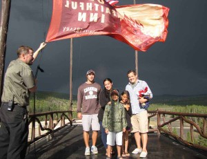 Bellman Ed Nabors displays an Old Faithful Inn flag atop the hotel during a trip to Yellowstone National Park by Nathan Bartlett, 8, center, and his family. (NPS photo by Dan Hottle - click to enlarge)