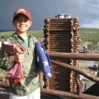 Nathan Bartlett, 8, holds two flags given to him by Xanterra Parks & Resorts atop the Old Faithful Inn in Yellowstone National Park. (NPS photo by Dan Hottle - click to enlarge)