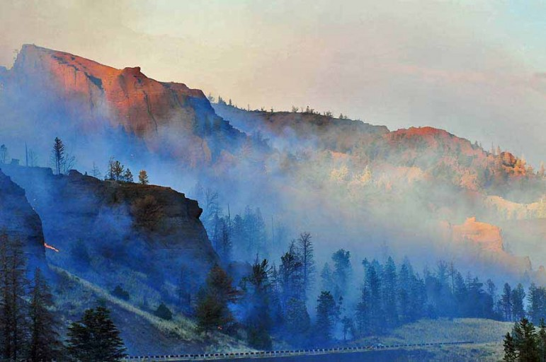 Smoke and sunlight create deep, surreal colors during the 2008 Gunbarrel Fire, which burned along the eastern boundary of Yellowstone National Park.