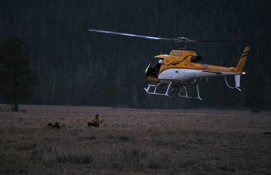 A search and rescue helicopter lands at the Jenny Lake rescue cache near Lupine Meadows in Grand Teton National Park on Saturday after completing a short-haul extraction of an imperiled climber from the Teewinot Mountain area. (Yellowstone Gate/Ruffin Prevost - click to enlarge)