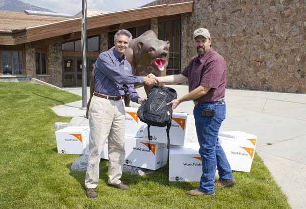 Jim McCaleb, left, general manager of Xanterra Parks & Resorts' Yellowstone operations, presents packpacks full of school supplies in Gardiner, Mont. (courtesy photo)
