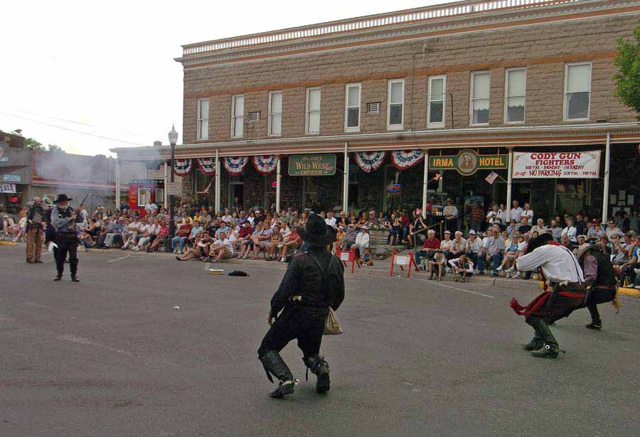 A crowd watches from the porch of the Irma Hotel in Cody as three villains are shot in a mock gunfight. (Ruffin Prevost - Yellowstone Gate file photo - click to enlarge)