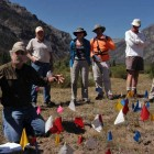 Archaeologist Larry Todd, kneeling, shows dozens of artifacts marked with small flags in the Shoshone National Forest during a July field trip sponsored by the Greater Yellowstone Coalition. (Ruffin Prevost/Yellowstone Gate - click to enlarge)