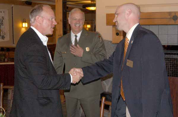 Wyoming Gov. Matt Mead, left, shakes hands with Cody Country Chamber of Commerce Executive Director Scott Balyo as Yellowstone National Park Superintendent Dan Wenk looks on. The men were among those attending a luncheon Friday at Old Faithful Lodge to mark the end of National Travel and Tourism Week and the successulf cooperative effort to plow park roads. (Ruffin Prevost/Yellowstone Gate)