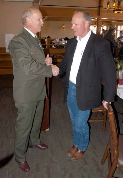 Yellowstone National Park Superintendent Dan Wenk, left, shakes hands with Wyoming Gov. Matt Mead on Friday during a luncheon at Old Faithful Lodge to mark the end of National Travel and Tourism Week and the successulf cooperative effort to plow park roads. (Ruffin Prevost/Yellowstone Gate)