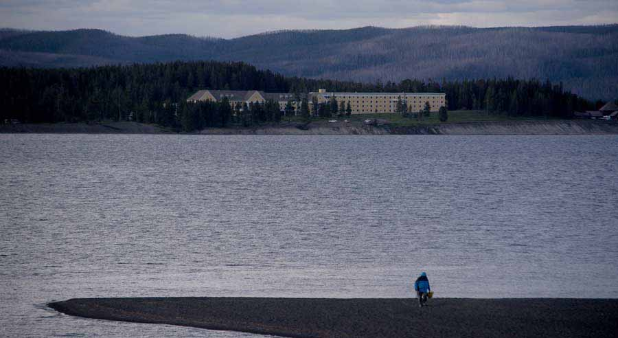 A beachcomber walks along the shore of Yellowstone Lake in view of Lake Hotel as the evening light fades in Yellowstone National Park. (Ruffin Prevost/Yellowstone Gate)