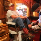 Tim Tetley works on Gordon Little's boots at Tetley's shoe-shine stand in the Cowboy Bar in Jackson, Wyo., south of Grand Teton National Park.