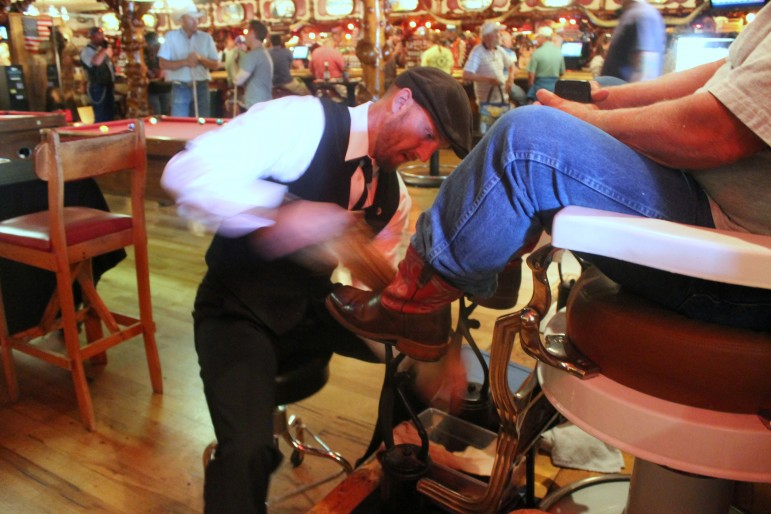 Tim Tetley shines a pair of boots at the Cowboy Bar in Jackson, Wyo., south of Grand Teton National Park.
