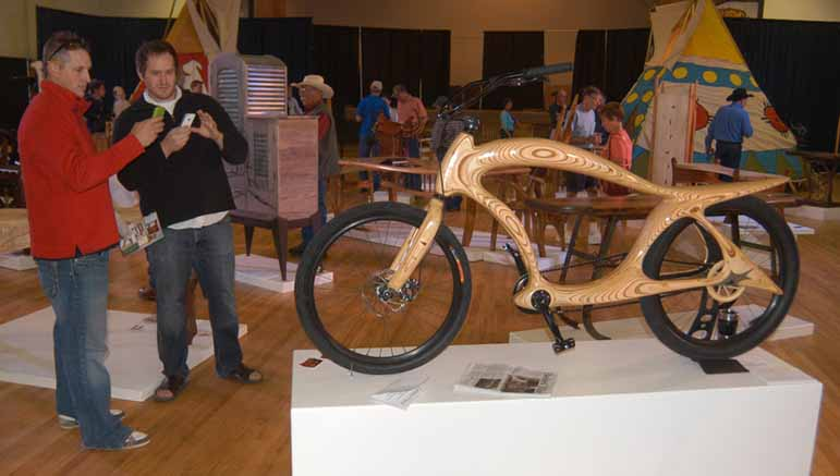 Jake Jones, left, and Dan Neilsen photograph a wooden bicycle created by Powell, Wyo. craftsman Ati Bekes during a visit Saturday to the Cody High Style exhibition in Cody, Wyo.