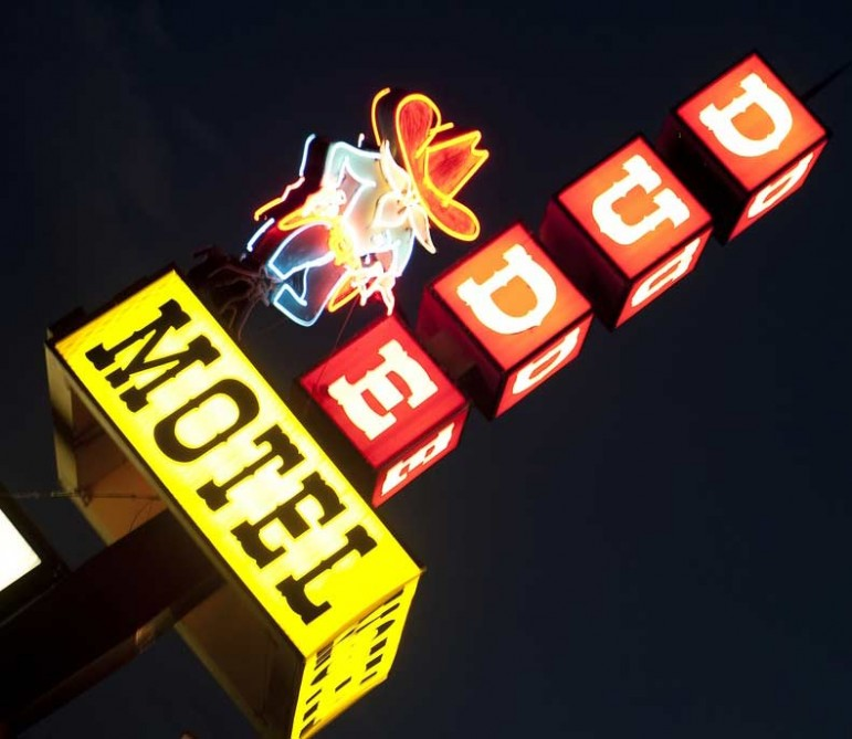 The Dude Motel sign lights up the night sky in West Yellowstone, Mont., where tourism has dropped sharply since the government shutdown closed Yellowstone National Park.