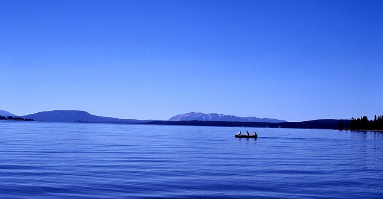 Three people share a canoe on Yellowstone Lake in Yellowstone National Park.
