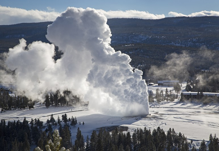 Rising steam from Old Faithful hangs in the frigid air as seen from Observation Point in Yellowstone National Park during February 2014 cold snap.