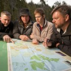 "From left, Cliff Barackman, James Fay, Ranae Holland and Matt Moneymaker consult a map during an episode of ""Finding Bigfoot."""