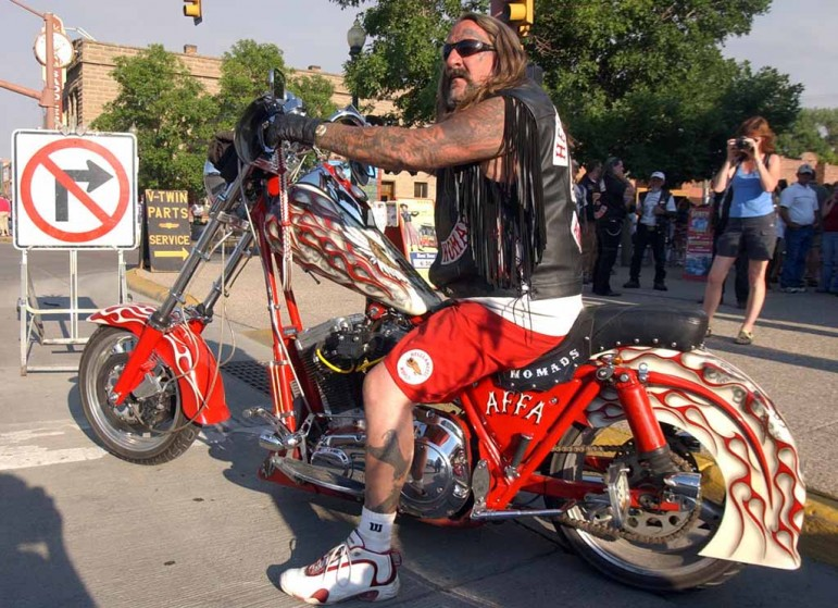A Hells Angels member from Arizona checks traffic  before pulling onto Sheridan Avenue during the group's 2006 World Run in Cody, Wyo.