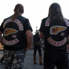 A Hells Angels motorcycle club member from Austria and one from Germany watch a mock gunfight at the Irma Hotel in Cody, Wyo. during the group's 2006 World Run this week.