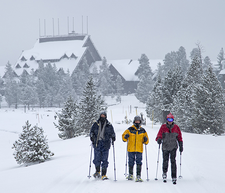 Old Faithful Inn is visible in the background as winter travelers in Yellowstone National Park head out for a trip to Black Sand Pool.
