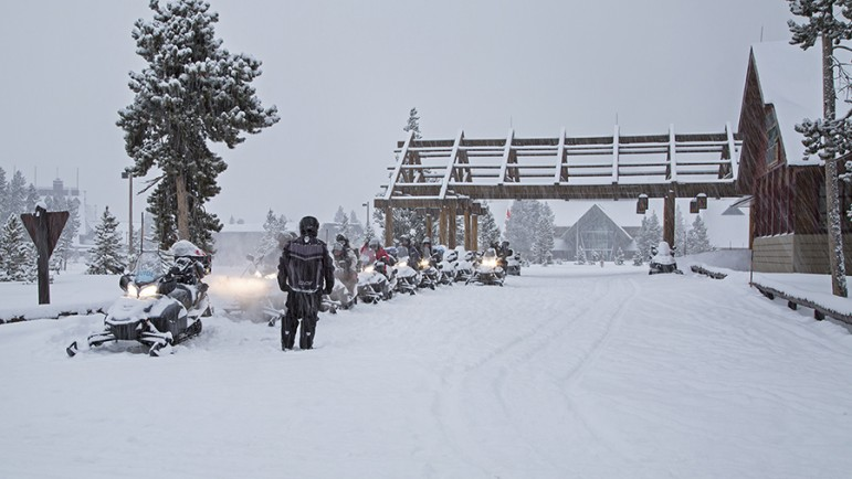 Riders line up their snowmobiles outside the Old Faithful Snow Lodge in Yellowstone National Park.
