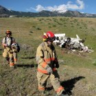 Emergency personnel walk past the wreckage of a crashed airplane Monday after the injured pilot was transported for medical care.