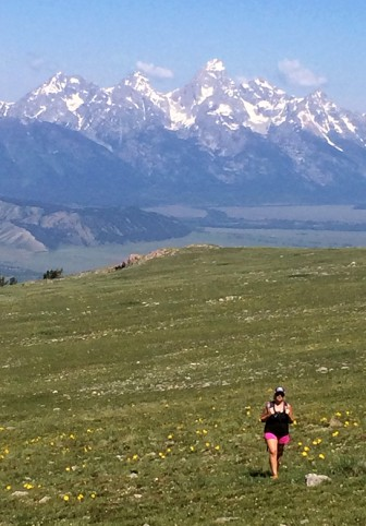 The Tetons loom in the background as hiker Cara Rank walks through a grassy meadow on Sheep Mountain in Jackson Hole.