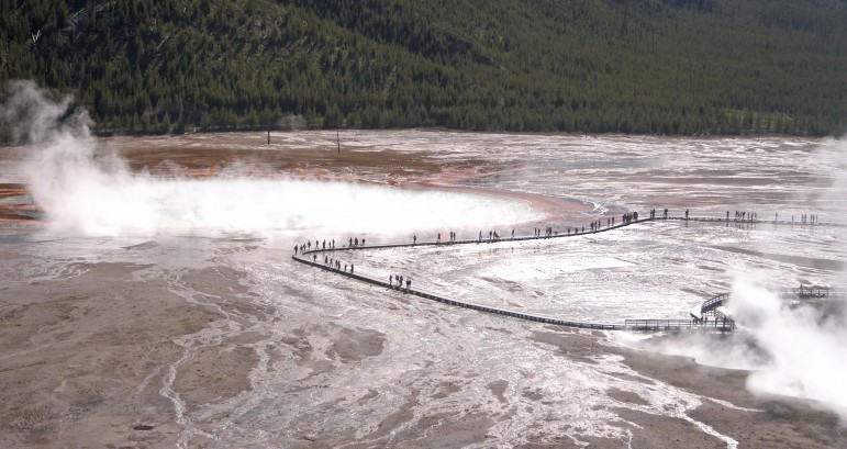 Visitors walk along the boardwalk past Grand Prismatic Spring in the Midway Geyser Basin in Yellowstone National Park. (Ruffin Prevost/Yellowstone Gate)
