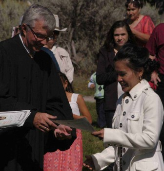 Grace Dolbear of Colstrip, Mont. accepts her certificate of citizenship from U.S. Magistrate Judge for the District of Wyoming Mark Carman during a Sept. 3 naturalization ceremony at Mammoth Hot Springs in Yellowstone National Park.