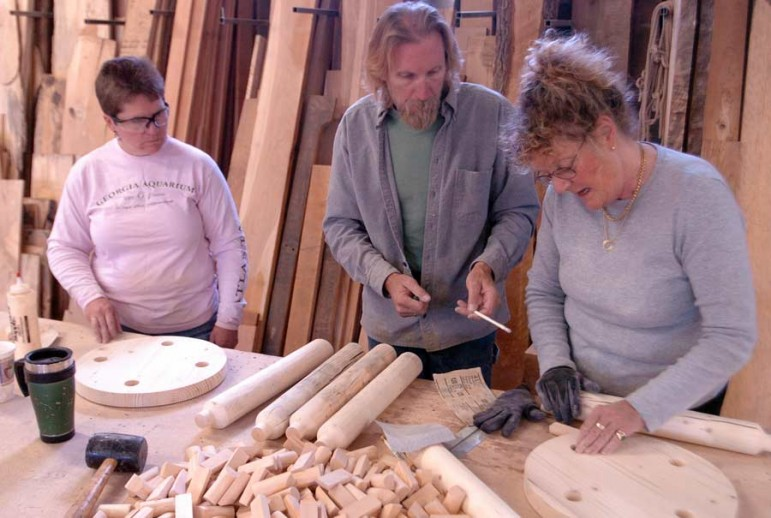 Liz Holmes, left, looks on as furniture designer John Gallis helps Hilary Heminway build a stool during a 2008 workshop as part of the Cody High Style show. Gallis coached a dozen students at his Norseman Designs West workshop on how to create a stool in the style of Western design pioneer Thomas Molesworth.