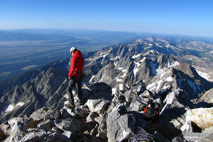 A climber on the summit of the Grand Teton in Grand Teton National Park surveys the Jackson Hole valley below.