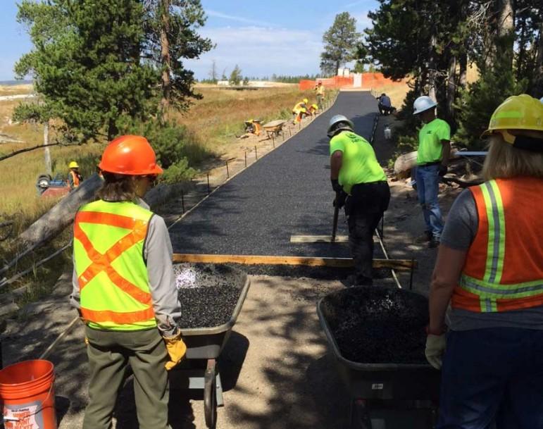 Volunteers help resurface a walking path near Old Faithful geyser in Yellowstone National Park.