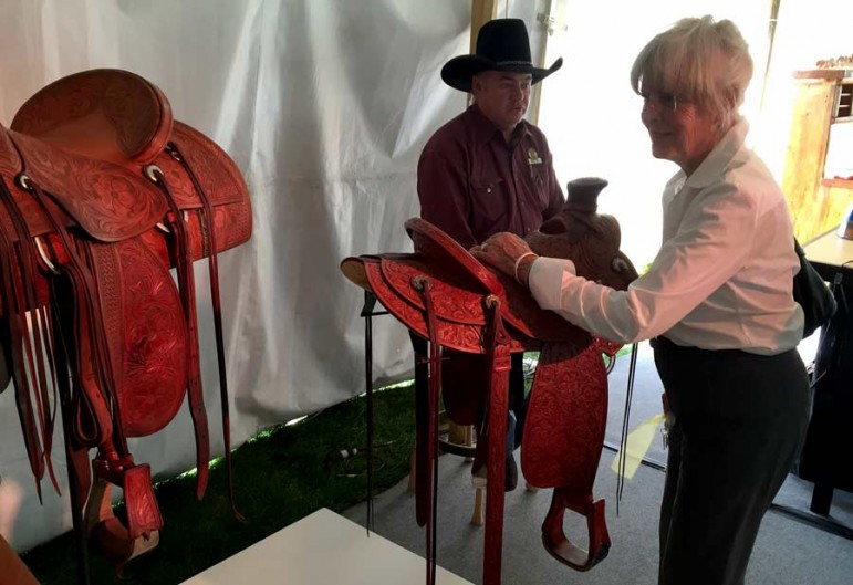 Western design enthusiast Ann Simpson chats with saddle maker Keith Seidel on Wednesday at the By Western Hands design exhibition in Cody, Wyo.