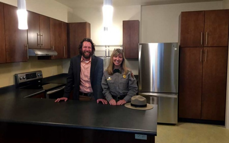 Dylan Hoffman, director of environmental affairs in Yellowstone for Xanterra Parks and Resorts, stands in the kitchen of a new employee housing unit near Old Faithful. He is joined by Julena Campbell, a spokeswoman for Yellowstone National Park.