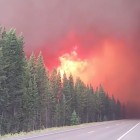 A frame from a video shot Wednesday shows the Berry Fire in Grand Teton National Park burning in heavy timber close to U.S. Highway 89. Officials have closed the road, which connects Grand Teton and Yellowstone National Park, resulting in the closure of Yellowstone's south entrance, as well as some trails, a campground and a lodge in Grand Teton. The closures may last several days, depending on fire activity, weather and other factors.