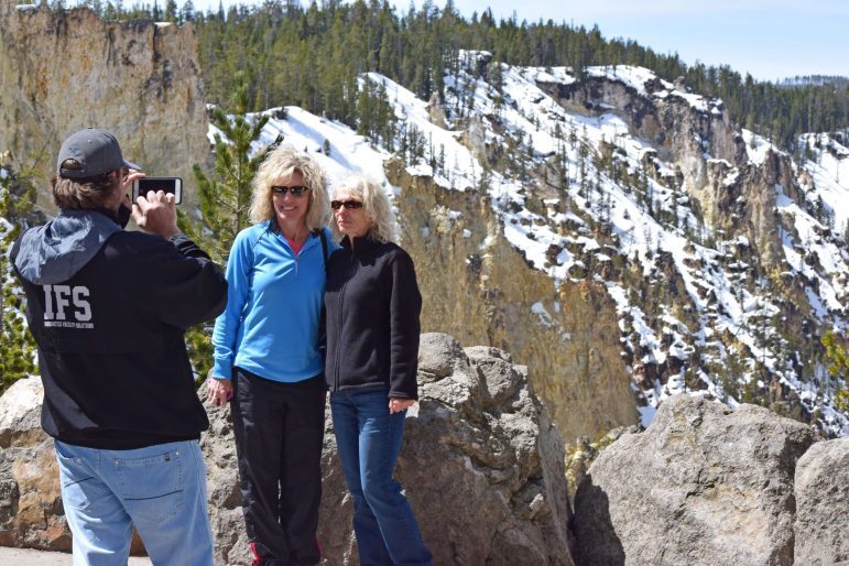 Jacob Baisley, who recently quit his job and sold his house to travel to national parks, snaps a photo May 4 of two Yellowstone National Park visitors at Artist Point.