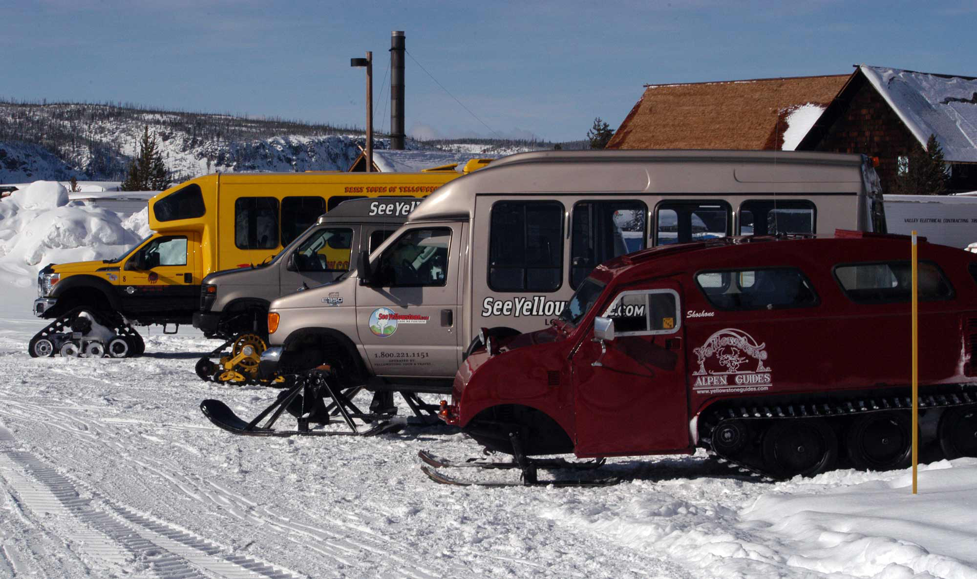 Snow coaches operated by private tour guide companies are parked near Old Fiathful Geyser in Yellowstone National Park. (Ruffin Prevost/Yellowstone Gate - click to enlarge)