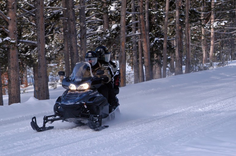 Two people share a snowmobile during a January 2012 trip into Yellowstone National Park.
