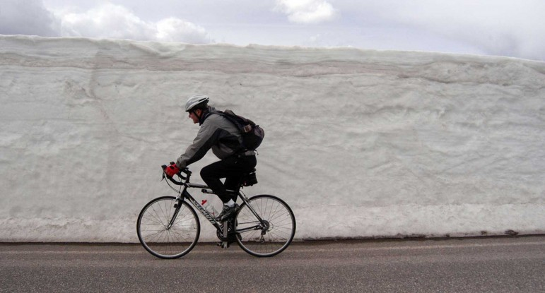 A bicyclist rides past freshly plowed snow along the road between Norris and Canyon Village in this 2012 file photo.