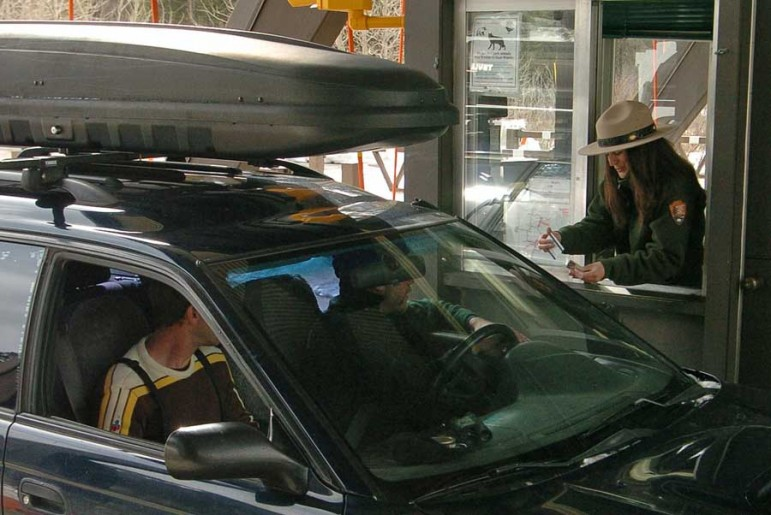 Candice Phipps, a worker at the East Gate to Yellowstone National Park, checks passes of visitors arriving from Cody in this 2012 file photo.