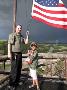 Nathan Bartlett, 8, helps Old Faithful Inn bellman Ed Nabors take down the American flag atop the hotel during a trip to Yellowstone National Park. (NPS photo by Dan Hottle - click to enlarge)