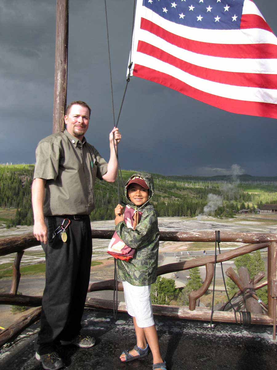 Nathan Bartlett, 8, helps Old Faithful Inn bellman Ed Nabors take down the American flag atop the hotel during a 2012 summer trip to Yellowstone National Park. (NPS photo by Dan Hottle - click to enlarge)