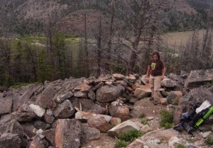 Researcher Mary Reiser surveys a the remains of a stone and wood structure in the Wood River area of the Shohone Forest in northwestern Wyoming east of Yellowstone Park. (Ruffin Prevost/Yellowstone Gate - click to enlarge)